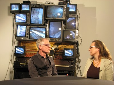 MoMA Educator Deborah Howes interviewing MoMA Conservator Glen Wharton in front of 'Untitled,' 1993 by Nam June Paik. Photo used with permission (c) MoMA 2013.
