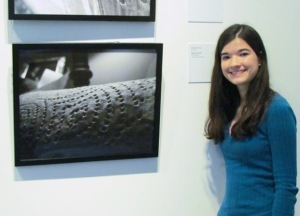 Elizabeth Moore, an NCVPS Photography student stands with her work in an exhibition in NCMA's education gallery. Courtesy North Carolina Museum of Art.
