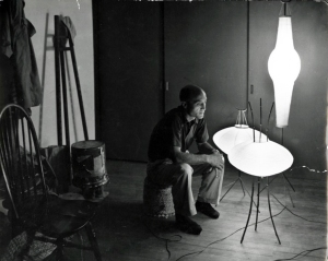 Isamu Noguchi seated with three Akari, c. 1950s. Image Courtesy of The Noguchi Museum