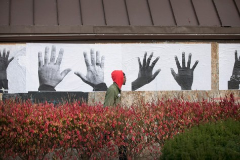St. Louis artist Damon Davis installs posters from his Push Forward Project on a boarded up business along West Florissant Street on November 19, 2014 in Ferguson, Missouri. Image from Zimbio.com. Source: Scott Olson/Getty Images North America