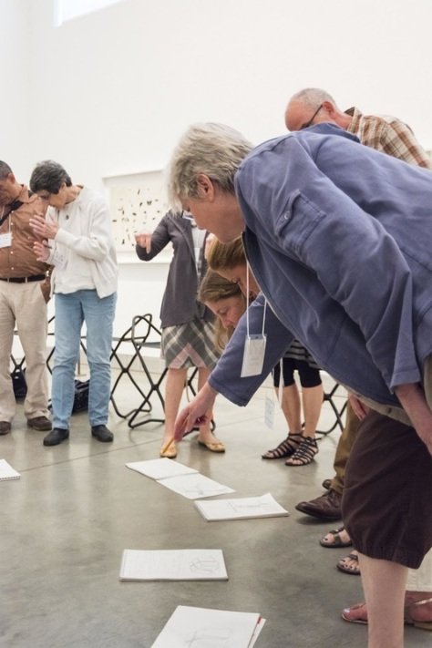 teachers looking at the drawings on the floor