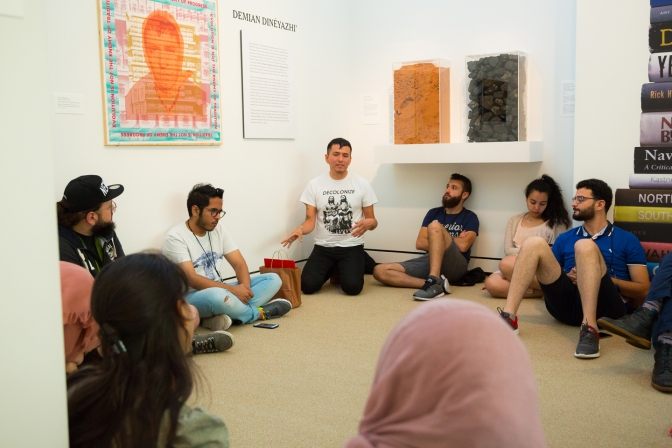 Artist Demian DinéYazhi' leading a conversation in the galleries with participants in the Middle East Partnership Initiative (MEPI) program.