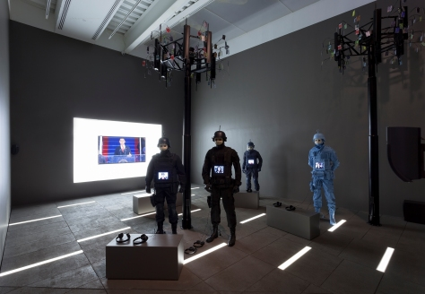 "installation view of Josh Kline's ""Freedom"" exhibition, showing a dark gallery with 4 police officer figures, a video screen in the rear, and 2 black poles rising up from the floor like trees."
